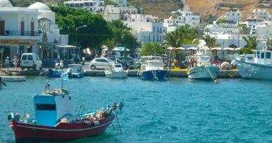 Heimwee naar Griekenland, een vissersbootje in het water voor een baai met Griekse huisjes